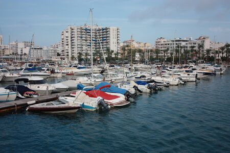 The port of Ibiza in Eivissa where boats and yachts are anchored in the VIP area of the Balearic island in the blue water in spain 免版税图像