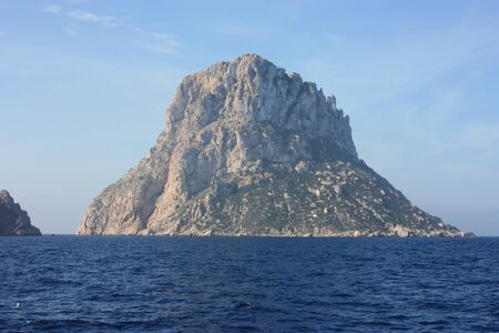 the islet of Es Vedra among the mist on the blue water of the ibiza sea in spain