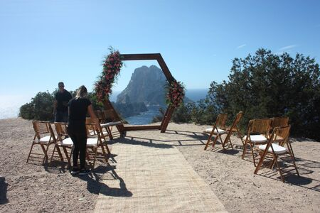 Getting married in Ibiza in summer. Dream wedding preparation in Cala D'Hort in front of the magical islet of Es Vedra to celebrate love on the seaside Banco de Imagens