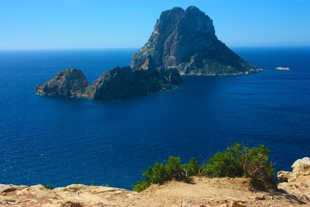The magical island of Es Vedra with the small islet of Es Vedranell next to it in front of the coast of Cala d'Hort in the tourist island of Ibiza in the midst of nature between cliffs, beaches and coasts in spain Imagens
