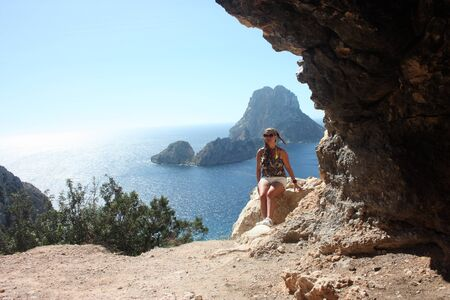 girl on a cliff in front of the magical island of Es Vedra in Cala d'Hort in the Ibiza Island Stock fotó