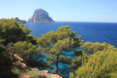 The solitary islet of Es Vedra in contrast against the blue sea of ​​Ibiza immersed in the green and arid wild nature in Spain