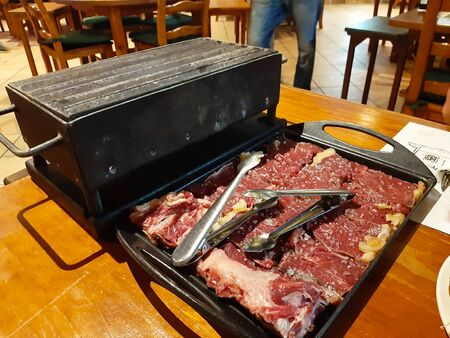 large slices of red ox meat with fat sprinkled with coarse salt on a grill lit to cook on a barbeque