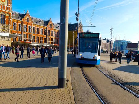 the tram at the dutch stop in front of the amsterdam train station in daylight in holland
