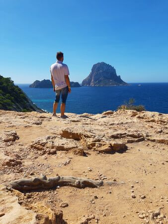 indistinct young man from behind enjoying the panorama of es vedra in summer at cala d'hort on the cliff in balearic island
