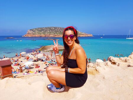 young caucasian brunette woman with a black dress on vacation in cala comte beach in ibiza island Stock fotó