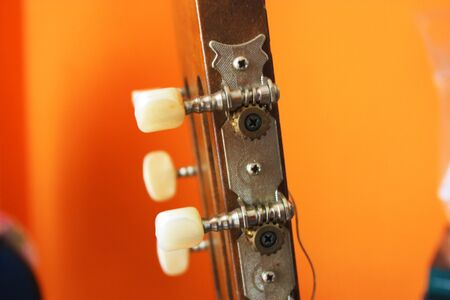 headstock with mechanics of a classical guitar with bright orange background 免版税图像