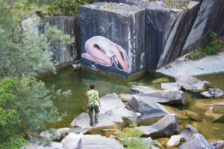 sticker of a kneeling woman attached to the wall of an abandoned marble quarry in tuscany landmark