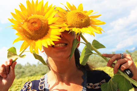 happy nice woman hides behind yellow blooming sunflowers in summer Stock Photo