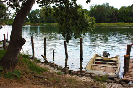 boat moored on the embankment of a river bank in the nature in tuscany