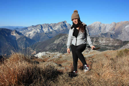 explorer girl on an adventurous excursion in the mountains of the Tuscan-Emilian Apennines. Apuan Alps on a beautiful sunny cold day