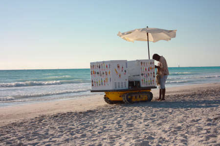 anonymous summer ice cream man with his cart on the sandy beach rests under the umbrella of his white crawler in rosignano tuscany