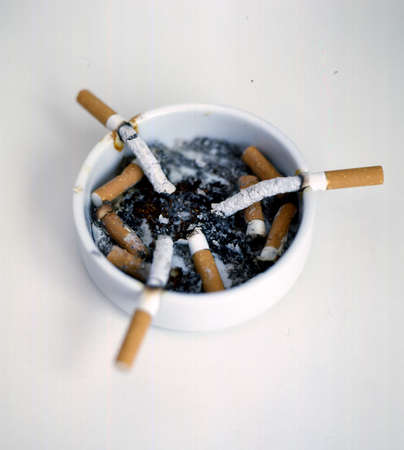 consumed: three cigarettes on a white ashtray consumed with their ashes