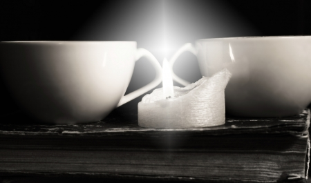 Monochrome image, two cups of coffee and candle
