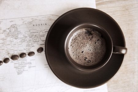 artwork  in grunge style,  cup of coffee, coffee beans and political map of the world photo