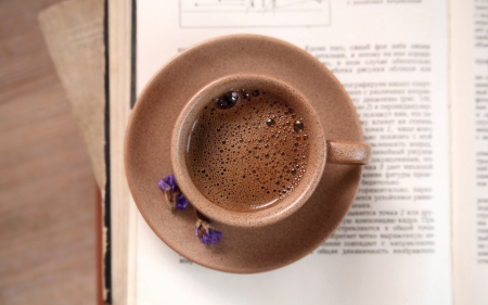 Ceramic cup of coffee, opened book and violet flowers, close up Stock Photo