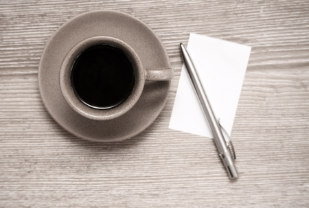 Toned image, cup of black coffee, pen and blank sheet of paper on wooden table photo