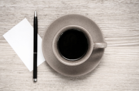 bisiness: Toned image, cup of black coffee, pen and blank sheet of paper on wooden table