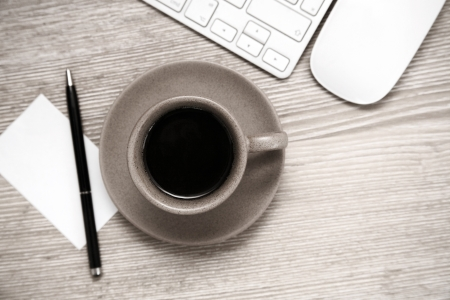 Toned image, cup of black coffee, pen, blank sheet of paper, mouse and  keyboard on wooden table 스톡 사진