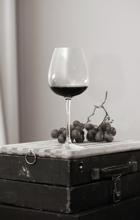 Monochrome image, glass of wine and grapes
