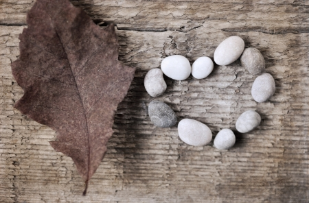 artwork  in retro style,  heart shape of stones, red leaf, wooden background