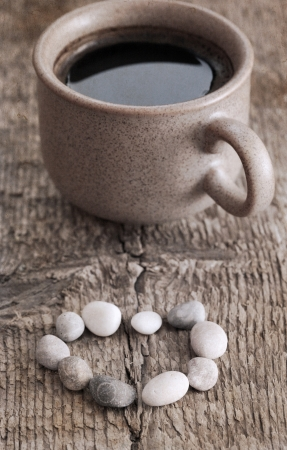 artwork  in retro style,  cup of coffee, heart shape of stones, wooden background