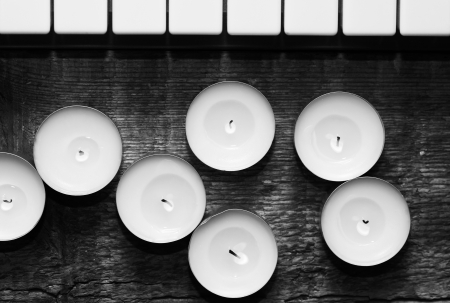 monochrome image, burning candles and pianoforte