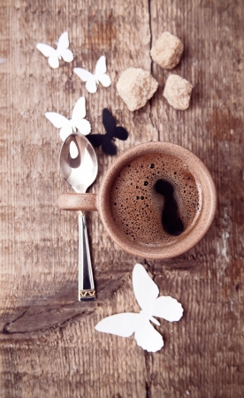Toned  image, cup of black coffee, brown sugar, spoon, paper butterflies on wooden table 스톡 사진