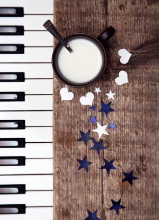 Toned image, cup of milk on wooden table, spoon, paper stars and hearts, pianoforte