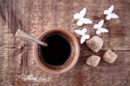 Toned  image, cup of black coffee, brown sugar, spoon, paper butterflies over wooden table. photo