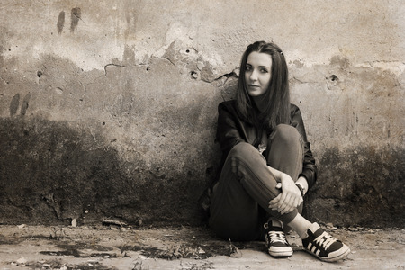 Artwork in retro style, young woman sitting near the rough wall