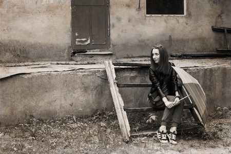 Artwork in retro style, young woman with umbrella sitting near the old house 스톡 사진