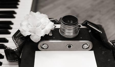 pianoforte: Artwork in retro style, old camera, film, piano, white flower Stock Photo