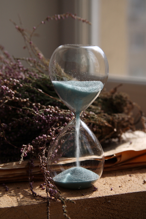 Time passing, sandglasses with blue sand, flowers, wood