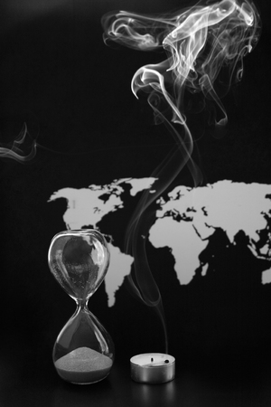 Monochrome image, world map, sandglass and burnt candle, match, black background Archivio Fotografico