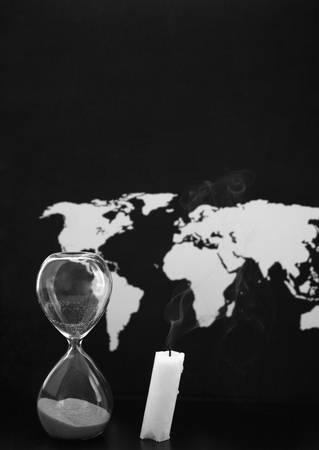 Monochrome image, world map, sandglass and burnt candle, black background