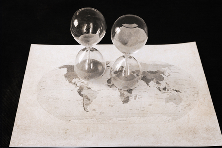 Artwork in retro style, two sandglasses, political map of the world, time passing