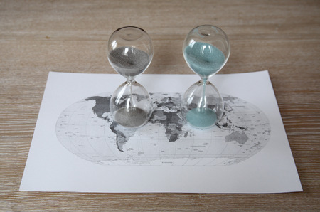 World political map and two sandglasses, time passing