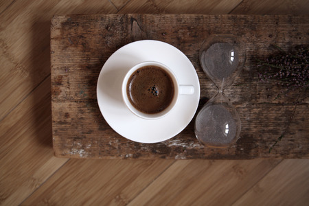 Coffee break, white cup of coffee, sandglass, wooden background, top view Archivio Fotografico