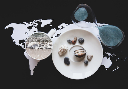 Collage in retro style, planning vacation/ world map, sandglass, cup with the sea inside and saucer with shells Archivio Fotografico