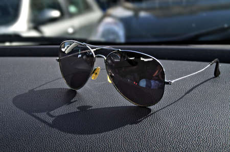 a pair of sunglasses on can dashboar making shade