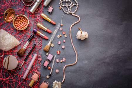 Women's cosmetics on a dark graphite background: pink lipstick of 3 shades, pink and peach eyeshadow, polka-dot powder, salt for baths, nail polish gently pink, mascara, a string of pink pearls. 免版税图像