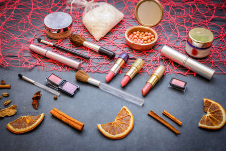 Women's cosmetics on a dark graphite background: pink lipstick of 3 shades, pink and peach eyeshadow, polka-dot powder, salt for baths, nail polish gently pink, mascara, a string of pink pearls. 写真素材