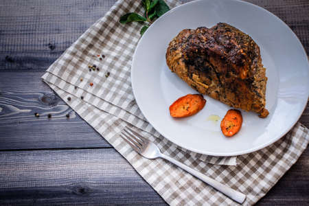 A piece of baked meat and slices of baked carrots on a white plate on a linen napkin in a cage on a dark gray tabletop