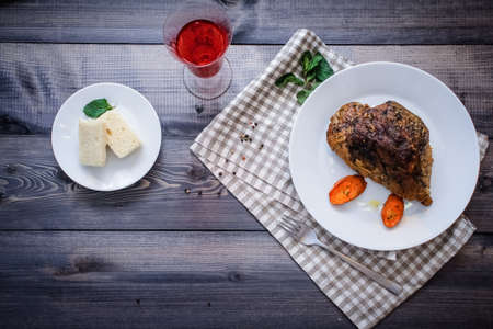 Baked meat in spices on a plate and carrots baked for a long time on a napkin on a dark gray countertop, next to a bakery tray rectangular pieces of white bread
