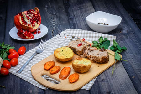 On the cutting board are two slices of baked meat, two slices of potatoes and baked carrot slices, a checkered napkin of flax, in a bowl are multi-colored peas of pepper and a cut pomegranate on a plate against the graphite tabletop