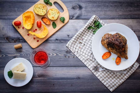 A piece of meat, sprinkled with spices, baked with baked carrot slices on a white plate, fork, linen checkered napkin, next to the baked slices of pumpkin, potatoes, spices and cherry tomatoes.
