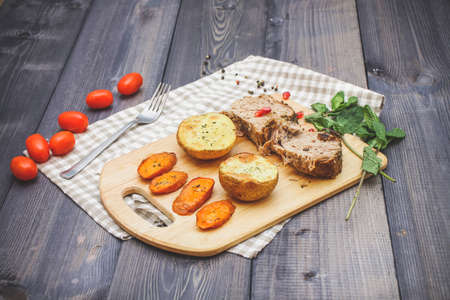 On the cutting board are two slices of baked meat, two slices of potatoes and baked carrot slices, a checkered napkin of flax, in a bowl are multi-colored peas of pepper and a cut pomegranate on a plate against the background of graphite countertops