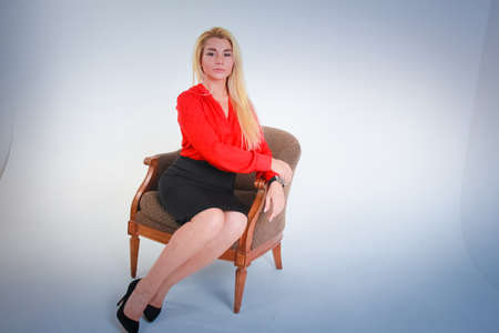 White to light blue gradient background. A girl in a red blouse in a black skirt sits in a chair arms folded. Stock Photo