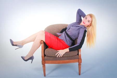 White to light blue gradient background. A girl in a red skirt in a gray jacket lies on a chair getting better with lowered hair.